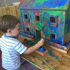 toddler boy painting dollhouse